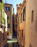 Stradella veneziana. Beautiful view of Venice narrow Canal and antique pier. sunny day cityscape with historical houses and traditional boat. Italy travel Royalty Free Stock Photo