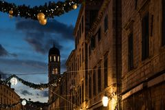 Stradun old street with bell tower decorated with Christmas lights and ornaments at dawn, Dubrovnik, Croatia. Stradun old street with bell tower decorated with Stock Photos