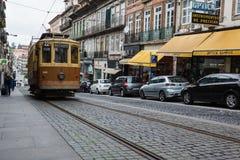 Straße Porto, Portugal, die eine alte braune und tan Laufkatze auf alten Kopfsteinen mit modernen Autos einer Reihe kennzeichnet Lizenzfreie Stockbilder