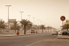 Straßenansicht mit Autos und Palmen, Staubsturm in Saudi-Arabien Stockbild