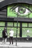 Straßenkunst in London Zwei junge Hippies unter einer Wand mit großem Auge Stockfoto