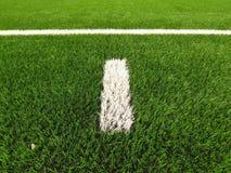 Straffområde Vit linje på konstgjort gräsfält på fotbolllekplats Detalj av ett kors av målade vita linjer Arkivbilder