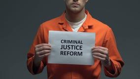 Straffrättreformuttryck på papp i händer av den Caucasian fången arkivfilmer