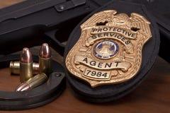 Strafverfolgungsausweis mit Gewehr, den Handschellen und den Kugeln Stockfotografie