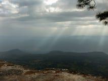 Strahl oder Strahl des Lichtes durch Wolke zum Wald auf Bergblick stockbild