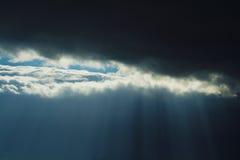 Strahlen der Leuchte durch dunkle Wolken Lizenzfreie Stockfotos