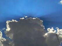 Strahlen der Sonne, die durch die dunklen Wolken auf dem Hintergrund des blauen Himmels bricht Lizenzfreies Stockfoto