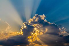 Strahlen der Sonne durch die flaumigen Wolken auf dem blauen Himmel Stockbild