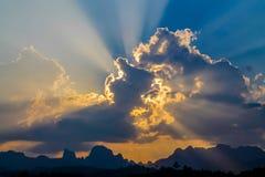 Strahlen der Sonne glänzen durch die Wolken auf blauem Himmel Stockbilder
