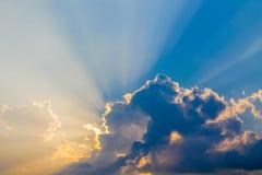 Strahlen der Sonne glänzen durch die Wolken auf dem blauen Himmel Stockfotografie