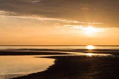 Strahlen des aufgehende Sonne über dem Ozean Stockfotos