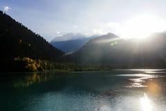 Strahlen des hellen Sonnenscheins über Gebirgssee Lizenzfreie Stockfotos