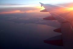 Strahlen des Lichtes in der purpurroten orange Himmelansicht des Dämmerungssonnenuntergangs vom Fensterflugzeug beflügelt Lizenzfreies Stockfoto