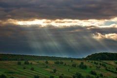 Strahlen des Lichtes von der Sonne durch graue Wolken auf grünen Feldern lizenzfreie stockfotografie