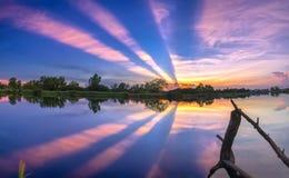 Strahlen des Sonnenuntergangs entlang Fluss, wenn die Sonne untergeht Lizenzfreies Stockfoto