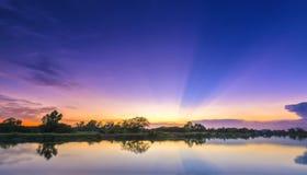 Strahlen des Sonnenuntergangs entlang Fluss, wenn die Sonne untergeht Stockbilder