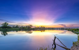 Strahlen des Sonnenuntergangs entlang Fluss, wenn die Sonne untergeht Lizenzfreie Stockbilder