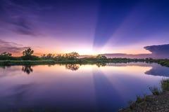 Strahlen des Sonnenuntergangs entlang Fluss, wenn die Sonne untergeht Stockfotografie