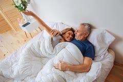Strahlende Frau, die breit beim Aufwachen nahe ihrem Mann lächelt lizenzfreie stockfotografie