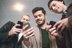 Strahlende Freunde, die am Telefon aufpassen stockfotografie
