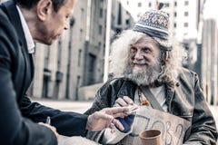 Strahlender beeindruckter grau-haariger armer Mann, der dankbar Geld empfängt stockfoto