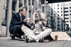 Strahlender schöner Mann, der angenehmes Gespräch mit schmutzigem Obdachlosem hat stockfoto