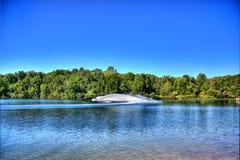 Strahlenski auf einem blauen See stockbild