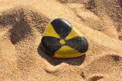 Strahlungszeichen malte Farben auf einem Stein auf dem Strand Lizenzfreies Stockfoto