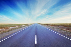 Straight as an arrow road goes at the plain Stock Photo