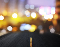 Straight asphalt road with marking lines. And reflections with colorful unfocused lights on a background Royalty Free Stock Photography