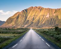 Straight asphalt road with mountain landscape against blue sky Royalty Free Stock Image