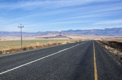 Straight Asphalt Road with Mountains in Background Stock Image