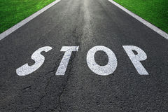 Straight asphalt road with stop message sign Royalty Free Stock Images