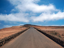 Straight asphalt road to the top of the mountain over the horizon. White clouds on a blue sky. Lanzarote Royalty Free Stock Photos