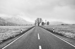 Straight  asphalt way between meadows. April weather. Wet snow in grass Royalty Free Stock Photo