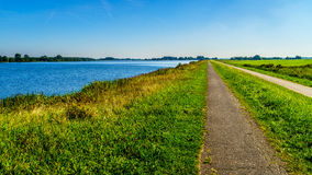 Straight bicycle path over the dike along the the bird sanctuary of Veluwemeer Stock Images