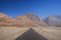 Straight black road to mountains Stock Photo