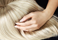 Straight blond wig brushing by a woman Stock Images