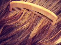 Straight brown hair with wooden comb closeup Stock Photo