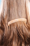 Straight brown hair with wooden comb closeup Royalty Free Stock Photos