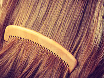 Straight brown hair with wooden comb closeup Royalty Free Stock Photo