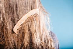Straight brown hair with wooden comb closeup Royalty Free Stock Images