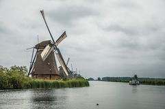 Straight canal with windmills and boat in a cloudy day at Kinderdijk. Situated in a polder, has the largest concentration of old windmills in the country Stock Images