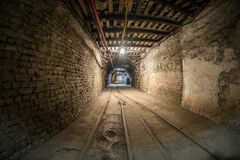 Straight corridor in underground mine. Fisheye view of narrow corridor in modern coal mine, tracks and elements of internal infrastructure visible royalty free stock images