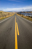 Straight country highway with yellow markings. Receding into the distance alongside a lake towards low hills under a blue sky stock image