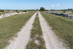 Straight country road surrounded with stone walls Stock Photo