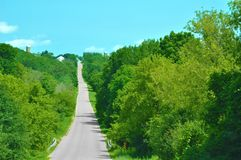 Straight Country Road through the trees Stock Photo