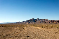 Straight Desert Dirt Road in California. A desert highway leading to a distant mountain range in California. The plan is very flat and only small shrubs manage Royalty Free Stock Photos