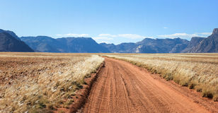 Straight desert dirt road track passes grassland towards mountains. Straight desert dirt road track pass a dry and sandy savanna plain towards mountain range Royalty Free Stock Images