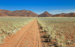 Straight desert dirt road track passes grassland towards mountains. Stock Photography